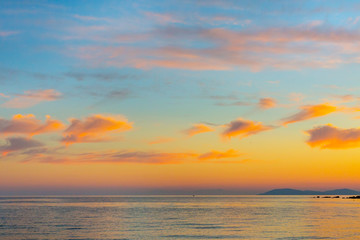 Golden sunset over sea in Greece coast with orange clouds