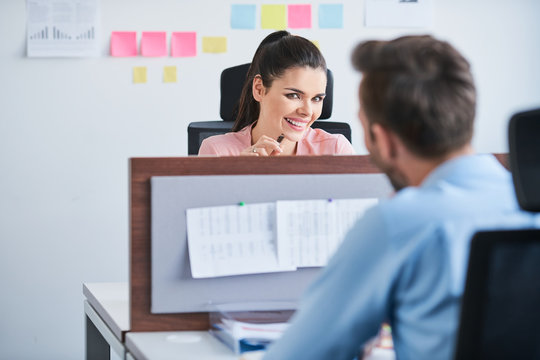 Office flirt - attractive woman flirting over desk with her coworker