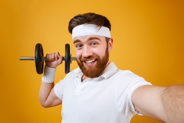 Happy young man make selfie with dumbbell. Looking at camera