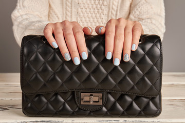 Fototapete - Classic black leather handbag and woman's hands with a nice manicure.