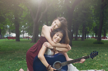Two happy boho chic stylish girlfriends with guitar, picnic