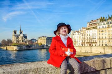 girl on embankment near Notre Dame de Paris with Christmas gift