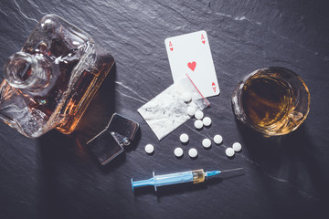 Hard drugs and alcohol on dark stone background