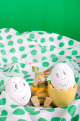 Easter eggs with funny faces near bunny on polka dot tablecloth. Emoji funny egg.