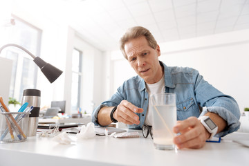 Handsome serious man holding glass with mixture