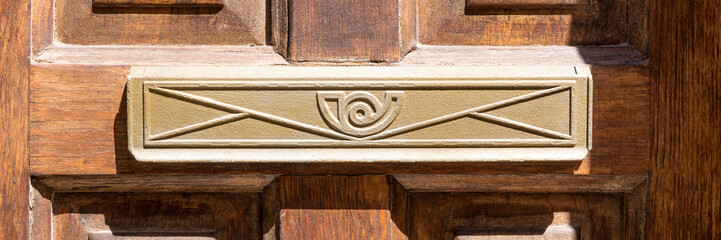 Closeup of letter box in brown wooden door