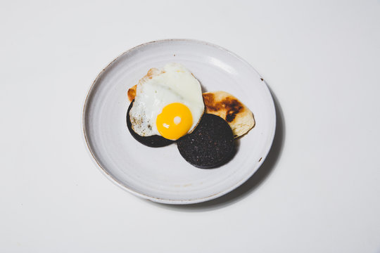Fried egg with black pudding on white background