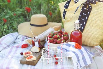 Deurstickers Picknick Basket, sandwiches, plaid and juice in a poppy field.