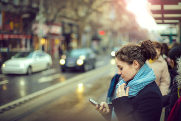 Girl using her phone while waiting in the street Fotomurales