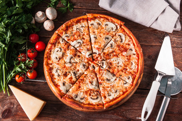 Traditional italian cuisine. Appetizing fresh pizza with mushrooms served on wooden background with ingredients and special knife, flat lay.