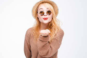 Young fashionable attractive hipster girl in sunglasses and straw hat sends air kiss to camera. Nice playful and happy woman with red lips on grey background with copy space.
