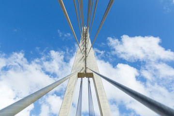 From below shot of bridge structure with wires on background of blue clear sky