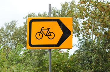 Fahrrad auf gelbem Schild zeigt Radweg an