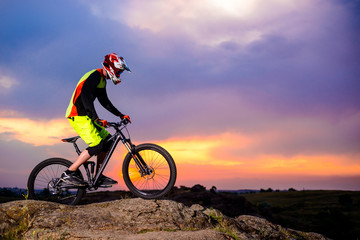 Professional Cyclist Riding the Bike on the Rock at Sunset. Extreme Sport Concept. Space for Text.