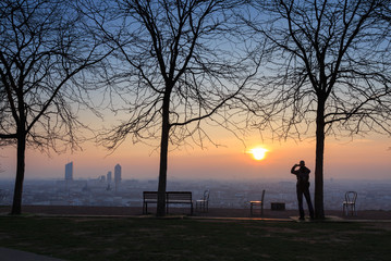Man photographing the sunrise over a city in a park. Lyon, France.
