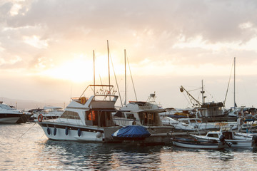 Yachts are moored in the sea against the sunset sky with clouds, evening
