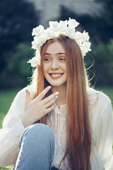 Beautiful redhead young woman laughing in surprise in the summer sunset park