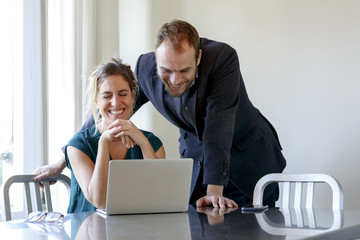 Mid adult couple at home, woman using laptop, man looking over her shoulder