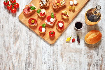 Mix of appetizers / snacks. Mediterranean tapas or antipasti on a rustic wooden table. Sandwiches with salami, jamon, sardines, salmon, cheese, tomato, olives, pepper, basil. Red wine. Copy space.