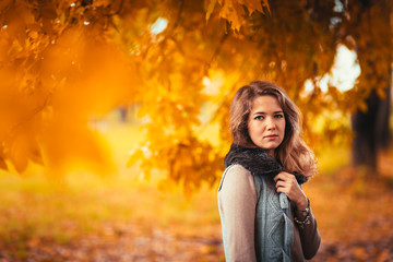 Portrait of a young girl in fur vest on background autumn park