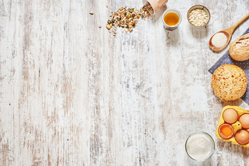 Baking background. Set of fresh bread, wholegrain flour, olive oil, eggs in a carton tray, wooden spoon, grains and seeds over light wooden table. Copy space.