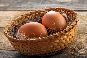 Two fresh farm chicken eggs in a rustic basket on a wooden table. Close-up shot.