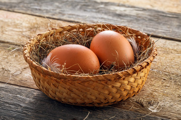 Couple of big chicken eggs in a basket on a wooden background. Close-up shot.