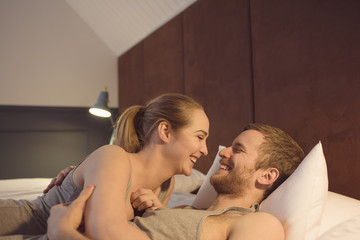 Young couple in bed, hugging, face to face, smiling