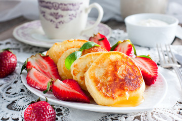 Homemade fritters with honey and strawberries, horizontal