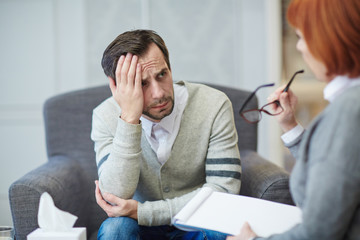 Mature female psychiatrist with clipboard in hands sitting next to her depressed patient and suggesting him possible solution of problem