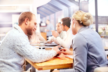 Businesswoman and man using smartphone touchscreen at office meeting