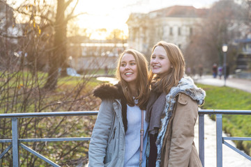 Two young women looking out from park bridge
