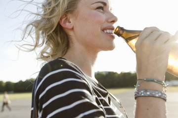 Mid adult woman drinking bottled beer outdoors