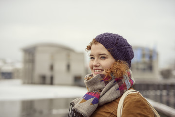 Portrait of woman outdoors, wearing hat and scarf