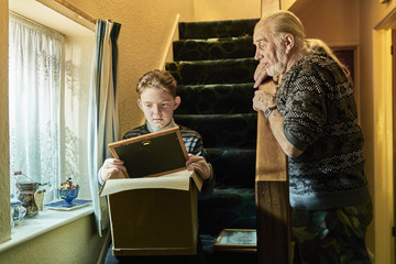 Senior man explaining to grandson sitting on stairs with photograph frame