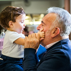 Senior man face to face with baby grandson in cafe