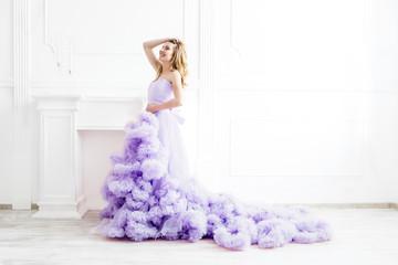 Dreamy woman portrait in a long pale purple ruffled gown in a white room. Elegant femininity