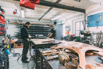 Two metalworkers working at forge workbench