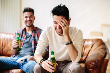 Male couple sitting on sofa, holding beer bottles, laughing