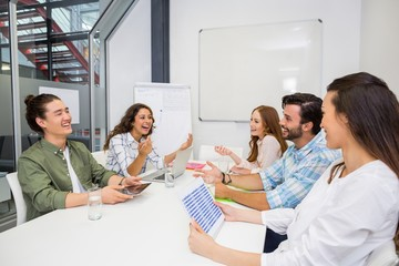 Smiling executive interacting during meeting in conference room