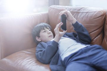 Boy playing with smartphone on sofa