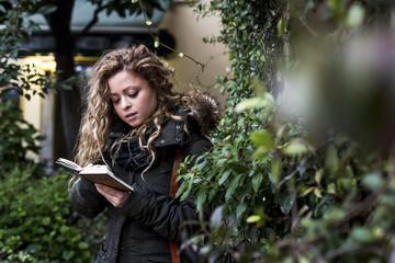 Woman in street reading book, Milan, Italy