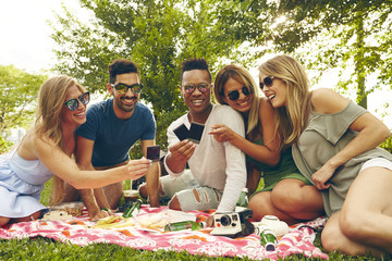 Five adult friends looking at film from instant camera at picnic in park