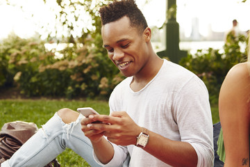 Young man looking at smartphone sitting in park