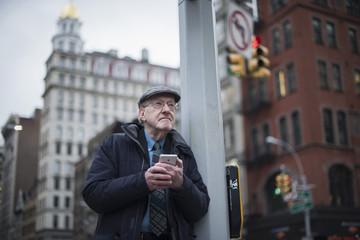 Man leaning against lamppost holding smartphone, Manhattan, New York, USA