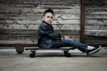 Boy sitting on skateboard