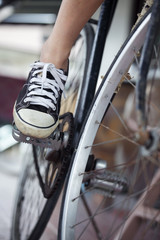 Person riding a vintage bicycle, close up view of sneaker shoe and the pedal