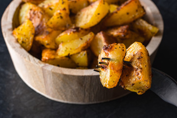 Roasted or backed potatoes in wooden bowl on black background