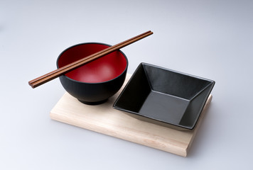 Chopsticks placed on a Chinese bowl with dish set arranged on a bamboo tray