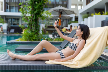 Woman taking selfie in swimming pool